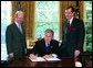 President George W. Bush signs the executive order establishing his Great Lakes Interagency Task Force, with EPA Administrator Michael Leavitt and James Connaughton, chairman of the Council on Environmental Quality, in the Oval Office Tuesday, May 18, 2004. The task force brings together ten agency and Cabinet officers to provide strategic direction on Federal Great Lakes policy, priorities and programs. White House photo by Paul Morse