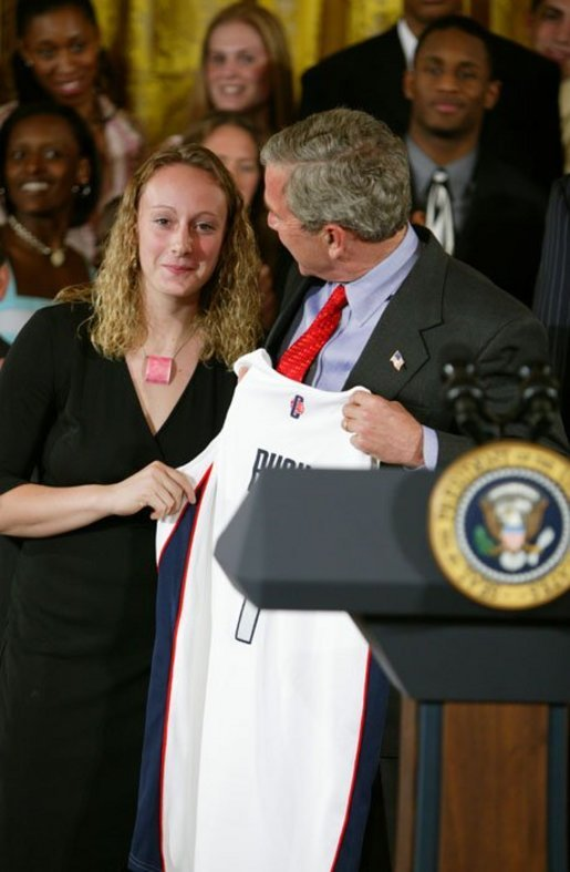 President George W. Bush stands with Maria Conlon of the University of Connecticut women's basketball team during a ceremony in the East Room congratulating four NCAA teams for winning national titles Wednesday, May 19, 2004. White House photo by Paul Morse.