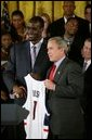 President George W. Bush stands with Emeka Okafor of the University of Connecticut's men basketball team during a ceremony in the East Room congratulating four NCAA teams for winning national titles Wednesday, May 19, 2004. White House photo by Paul Morse.