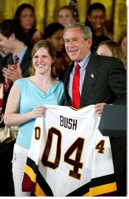President George W. Bush stands with Kelsey Bills of the University of Minnesota's women's hockey team during a ceremony in the East Room congratulating four NCAA teams for winning national titles Wednesday, May 19, 2004.  White House photo by Paul Morse