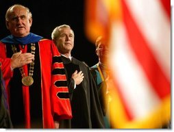 President George W. Bush stands on stage with LSU President William Jenkins during the singing of the National Anthem before delivering remarks at the Louisiana State University Commencement in Baton Rouge, La., Friday, May 21, 2004.  White House photo by Eric Draper