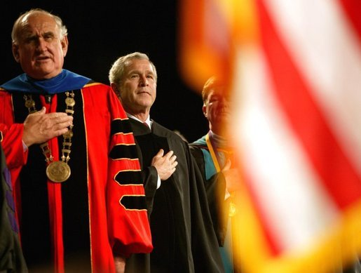 President George W. Bush stands on stage with LSU President William Jenkins during the singing of the National Anthem before delivering remarks at the Louisiana State University Commencement in Baton Rouge, La., Friday, May 21, 2004. White House photo by Eric Draper.