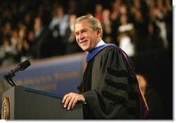 "President George W. Bush imparts some light-hearted audience to the graduating students at the Louisiana State University Commencement in Baton Rouge, La., Friday, May 21, 2004. ""As you enter professional life, I have a few other suggestions about how to succeed on the job. For starters, be on time. It's polite, and it shows your respect for others. Of course, it's easy for me to say,"" said the President. ""It's easy for me to be punctual when armed men stop all the traffic in town for you.""  White House photo by Eric Draper"