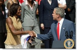 President George W. Bush greets Detroit Shock player Swin Cash during a photo opportunity with the 2003 WNBA champions in the Rose Garden on May 24, 2004.  White House photo by Paul Morse