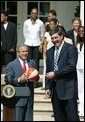 President George W. Bush is presented a signed ball from Detroit Shock coach Bill Laimbeer during a photo opportunity with the 2003 WNBA champions in the Rose Garden on May 24, 2004. White House photo by Paul Morse.