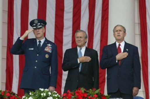 President George W. Bush, Secretary of Defense Donald Rumsfeld and Chairman of the Joint Chiefs of Staff General Richard B. Meyers look on as the National Anthem is played during Memorial Day commemorative ceremonies at Arlington National Cemetery in Arlington, Virginia Monday May 31, 2004. White House photo by Joyce Naltchayan.