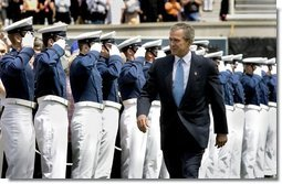 President George W. Bush walks to the stage while saluted by Air Force Cadets during his introduction at the United States Air Force Academy Graduation Ceremony in Colorado Springs, Colorado, June 2, 2004.  White House photo by Eric Draper