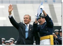 President George W. Bush celebrates with a graduating Air Force Cadet during the United States Air Force Academy Graduation Ceremony in Colorado Springs, Colorado, June 2, 2004.  White House photo by Eric Draper