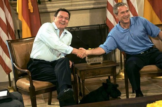 President George W. Bush and German Chancellor Gerhard Schroeder shake hands during their bilateral meeting at the G-8 Summit in Sea Island, Ga., Tuesday, June 8, 2004. Barney, is seen in foreground. White House photo by Eric Draper
