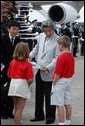 Arriving for the G8 summit at Sea Island, Ga., Japanese Prime Minister Junichiro Koizumi talks with children at Hunter Army Airfield in Savannah, Ga., June 8, 2004. White House photo by Paul Morse