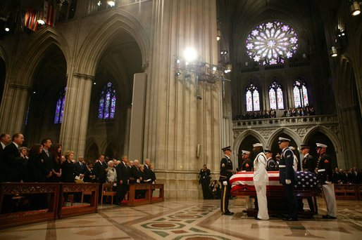 The casket of former President Ronald Reagan is surrounded by military service pall bearers at the funeral service at the National Cathedral in Washington, DC on June 11, 2004. White House photo by Paul Morse.
