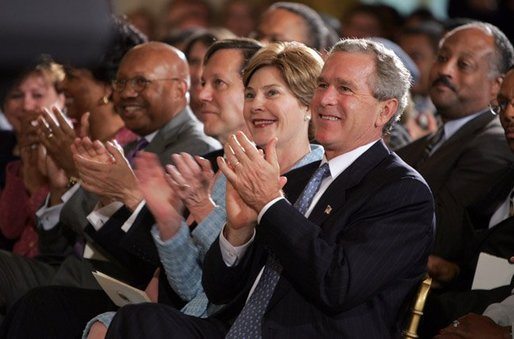 President George W. Bush and Mrs. Laura Bush applaud the performances of jazz musicians during a reception for Black Music Month in the East Room of the White House on June 22, 2004. White House photo by Paul Morse