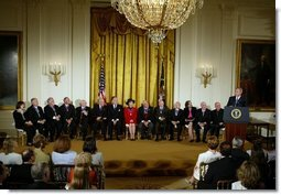 The recipients of the Presidential Medal of Freedom listen to President George W. Bush after receiving their awards in the East Room of the White House on June 23, 2004.  White House photo by Paul Morse