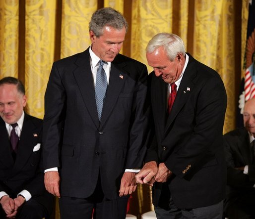 Recipient of the Presidential Medal of Freedom Arnold Palmer compares golf grips with President George W. Bush before receiving his award in the East Room of the White House on June 23, 2004. White House photo by Paul Morse