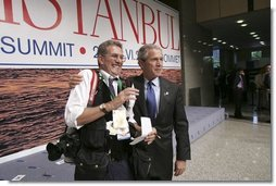 After participating in the official group photo of NATO leaders, President George W. Bush grabs Reuters photographer Larry Downing for a quick photo op of his own during the NATO Summit at the Istanbul Convention and Exhibition Center in Turkey, Monday, June 28, 2004.