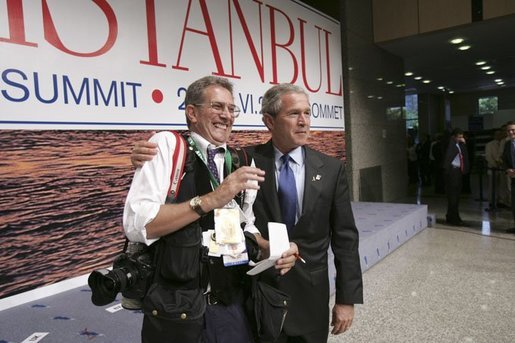 After participating in the official group photo of NATO leaders, President George W. Bush grabs Reuters photographer Larry Downing for a quick photo op of his own during the NATO Summit at the Istanbul Convention and Exhibition Center in Turkey, Monday, June 28, 2004. White House photo by Eric Draper.