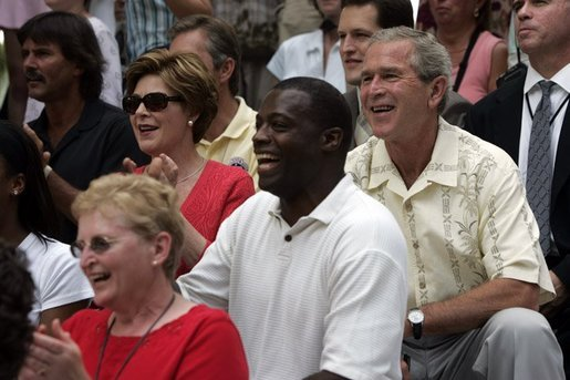President George W. Bush and First Lady Laura Bush watch the Challenger Phillies of M.O.T. Little League from Middletown, Delaware take on the Challenger Yankees of Lancaster County Little Leagues from Lancaster County, Pennsylvania with former NFL Washington Redskins player Darrell Green, center, at Tee Ball on the South Lawn at the White House on Sunday July 11, 2004. White House photo by Paul Morse.