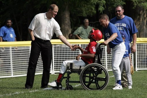 Former Major League pitcher Jim Abbott congratulates a player from the Challenger Phillies from Middletown, Delaware at Tee Ball on the South Lawn at the White House on Sunday July 11, 2004. White House photo by Paul Morse.