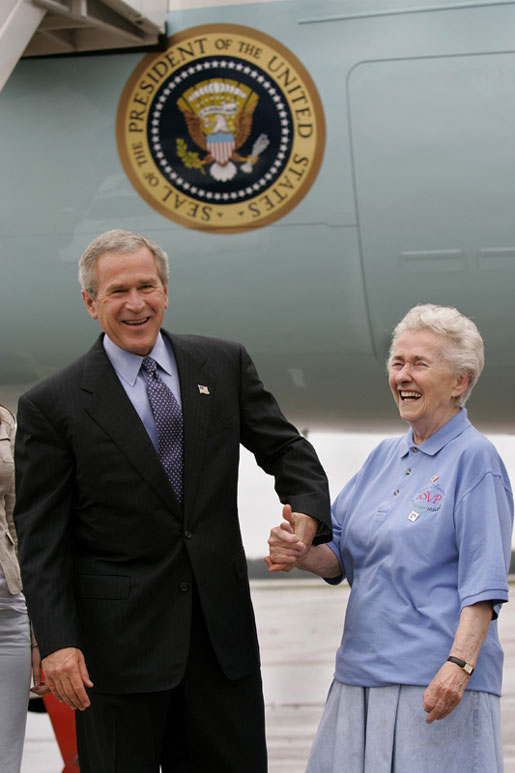 President George W. Bush meets USA Freedom Corps Greeter Grace McCarthy, 83, upon his arrival in Marquette, Mich., Tuesday, July 13, 2004. Ms. McCarthy has volunteered more than 4,000 hours with local groups, including the Retired and Senior Volunteer Program in Marquette. White House photo by Eric Draper