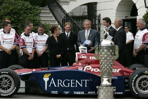 After being presented a racing helmet, President George W. Bush talks with Buddy Rice (center, left), the winner of 2004 Indianapolis 500, and his championship team, Rahal/Letterman Racing, during a visit to the South Lawn of the White House, July 19, 2004. White House photo by Paul Morse.