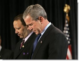 President George W. Bush joins Marc Morial, President of the National Urban League, in prayer on stage before delivering remarks in Detroit, Mich., Friday, July 23, 2004.  White House photo by Eric Draper