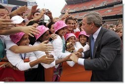 President George W. Bush is greeted by the Afghan girls soccer team after delivering remarks to the athletes at the International Children's Games and Cultural Festival in Cleveland, Ohio, July 30, 2004.  White House photo by Paul Morse