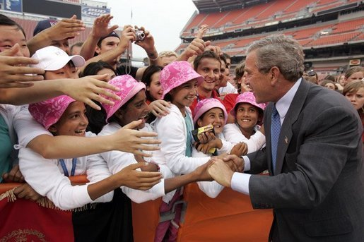 President George W. Bush is greeted by the Afghan girls soccer team after delivering remarks to the athletes at the International Children's Games and Cultural Festival in Cleveland, Ohio, July 30, 2004. White House photo by Paul Morse.