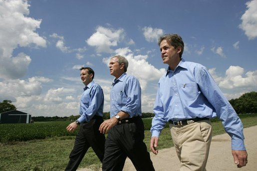 President George W. Bush walks with Minnesota Governor Tom Pawlenty, left, and Sen. Norm Coleman during a visit to the Katzenmeyer family farm in Le Sueur, Minn., Wednesday, Aug. 4, 2004. White House photo by Eric Draper.