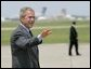 President George W. Bush waves as he walks across the tarmac to Air Force One before departing TSTC Airport in Waco, Texas, Wednesday, Aug. 11, 2004. White House photo by Eric Draper.