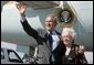 President George W. Bush waves to photographers with Freedom Corps Greeter Lucia Haas in front of Air Force One after his arriving in Phoenix, Arizona, Wednesday, Aug. 11, 2004. Hass, 73, spends two days a week as a volunteer at Surprise Senior Center in Surprise, Arizona, where she teaches English and Spanish Classes, calls Bingo games, instructs needlecraft and sewing classes and serves meals to seniors.  White House photo by Eric Draper