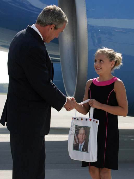 President George W. Bush visits with Freedom Corps greeter Alexandra Amend after arriving at Cincinnati/Northern kentucky International Airport Monday, Aug. 16, 2004. White House photo by Paul Morse.