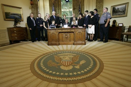 President George W. Bush delivers a Live Radio Address surrounded by Mrs. Bush and families of victims of 911 in the Oval Office, Saturday, Sept. 11, 2004. White House photo by Eric Draper