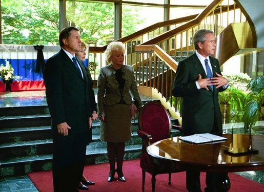 "After signing a condolence book for the victims of the recently attacked school in Beslan, Russia, President George W. Bush addresses the media as Ambassador Yuri Ushakov, far left, Laura Bush, and the Ambassador's wife, Svetlana Ushakova, listen at the Russian Embassy in Washington, D.C., Sept. 12, 2004. ""I'm here to express my country's heart-felt sympathies for the victims and the families who suffered at the hands of the evil terrorists. The United States stands side-by-side with Russia as we fight off terrorism, as we stand shoulder-to-shoulder to make the world a more peaceful place and a free place,"" said President Bush. White House photo by Paul Morse."