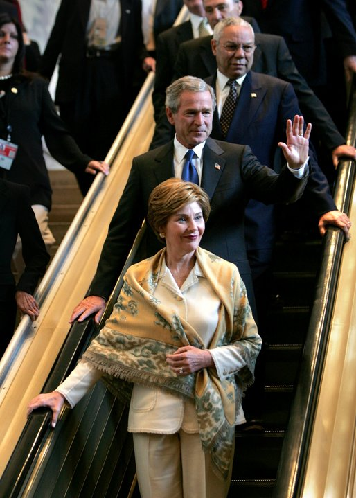 Descending the escalator with Laura Bush and Secretary of State Colin Powell, President George W. Bush waves to the international media after delivering his speech to the United Nations General Assembly in New York City Tuesday, Sept. 21, 2004. White House photo by Eric Draper.