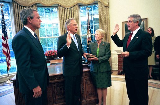 President George W. Bush observes Chief of Staff Andy Card swearing-in Porter Goss as the new director of the CIA in the Oval Office Friday, Sept. 24, 2004. Also pictured is Director Goss's wife Mariel. White House photo by Eric Draper.