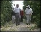 President George W. Bush walks with Pat McKenna through a hurricane-battered orange grove in Lake Wales, Fla., Wednesday, Sept. 29, 2004. Located in the heart of Florida's citrus country, almost half of the McKenna brothers' orange grove was destroyed by the hurricanes. White House photo by Eric Draper.