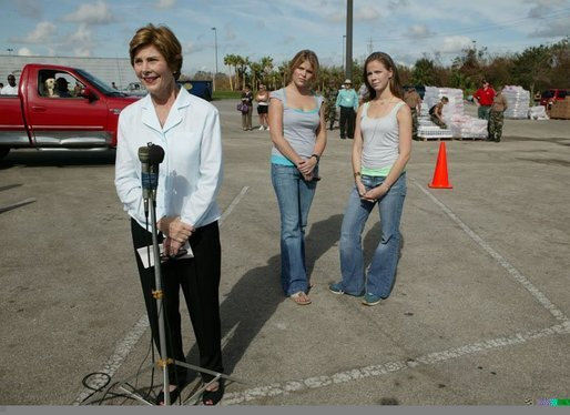 Laura Bush speaks to reporters after working with volunteers at the Indian River County Distribution Center as her daughters, Jenna and Barbara stand with her in Vero Beach, Fla., Friday, October 1, 2004. White House photo by Joyce Naltchayan.