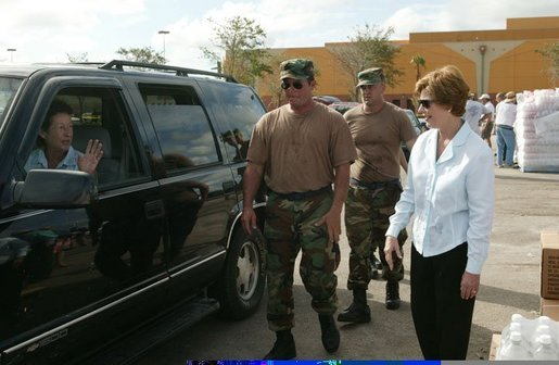 Laura Bush greets a local resident with members of the National Guard at the Indian River County Distribution Center where water, ice and Meals Ready To Eat (MRE) are passed out to residents recovering from Hurricanes Jeanne and Frances in Vero Beach, Fla., Friday, October 1, 2004. White House photo by Joyce Naltchayan.