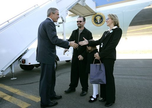 "President George W. Bush meets USA Freedom Corps Greeters Blake and Mona Schomas and their daughter Katherine at the Wilkes-Barre/Scranton International Airport in Avoca, Pa., Wednesday, Oct. 6, 2004. Mr. and Mrs. Schomas founded ""Home of Their Own,"" a sterile home environment where families can reside free of charge while their children recover from bone marrow transplant surgery. White House photo by Eric Draper."
