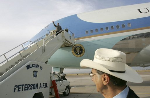 President George W. Bush waves as he arrives aboard Air Force One at Peterson Air Force Base in Colorado Springs, Colo., as USA Freedom Corps Greeters Bob Carlone waits to greet the President Tuesday, Oct. 12, 2004. White House photo by Eric Draper.