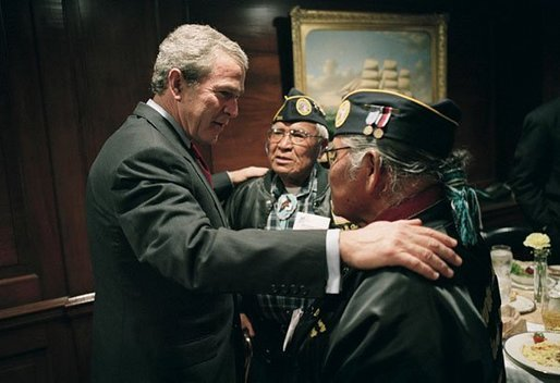 President George W. Bush talks with World War II Veterans Jose Ramos Chavez, left, and his younger brother Joe Diego Chavez, both of Albuquerque, N.M., during a breakfast with Secretary of Veterans Affairs Anthony Principi, Senator Bob Dole and World War II Veterans in the Executive Dining Room at the White House Friday, May 28, 2004. The brothers served in the Army during WWII. Jose took part in the D-Day invasion at Normandy, France, and Joe served in both the Atlantic and Pacific theaters. File photo. White House photo by Eric Draper.