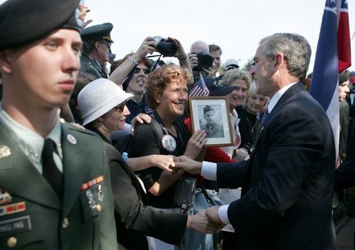 President George W. Bush meets with veterans and their families after delivering remarks during ceremonies marking the 60th anniversary of D-Day at the American Cemetery in Normandy, France, June 6, 2004. File Photo. White House photo by Eric Draper.