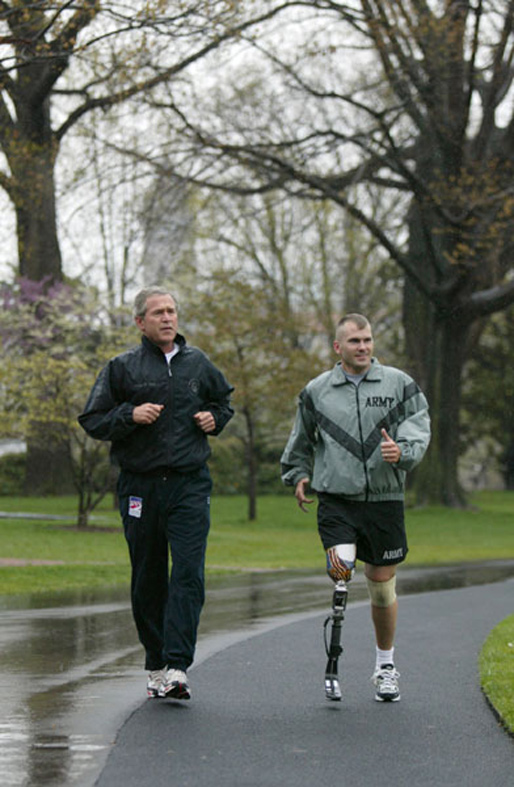 President George W. Bush runs with U.S. Army Staff Sergeant Michael McNaughton, of Denham Springs, La., on the South Lawn April 14, 2004. The two met Jan. 17, 2003, at Walter Reed Army Medical Center, where SSgt. McNaughton was recovering from wounds sustained in Afghanistan. The President wished SSgt. McNaughton a speedy recovery so that they might run together in the future. White House photo by Eric Draper.