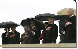 President George W. Bush and Laura Bush stand at attention with, from left, former President Jimmy Carter and First Lady Rosalynn Carter; former President George H.W. Bush and First Lady Barbara Bush; and former President Bill Clinton, Chelsea Clinton, and Sen. Hillary Clinton (not pictured) during the dedication ceremony of the William J. Clinton Presidential Center and Park in Little Rock, Ark., Nov. 18, 2004.  White House photo by Eric Draper