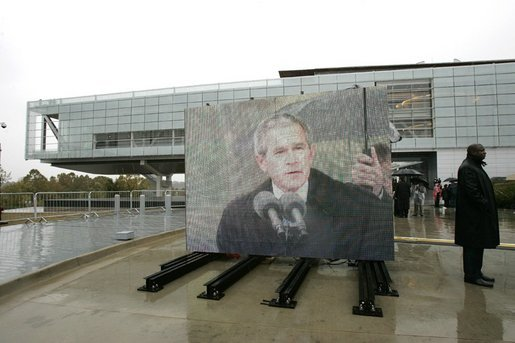 "As pictured on an outdoor video screen, President George W. Bush addresses attendees during the dedication of former President Bill Clinton's Presidential Center and Park in Little Rock, Ark., Nov. 18, 2004. ""He was a tireless champion of peace in the Middle East. He used American power in the Balkans to confront aggression and halt ethnic cleansing. And in all his actions and decisions, the American people sensed a deep empathy for the poor and the powerless,"" said President Bush. White House photo by Eric Draper."