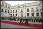 President George W. Bush walks with President Ricardo Lagos of Chile past a unit of Carabineros at the La Moneda Presidential Palace upon arrival for a meeting and private dinner in Santiago, Chile, Nov. 21, 2004. White House photo by Paul Morse.