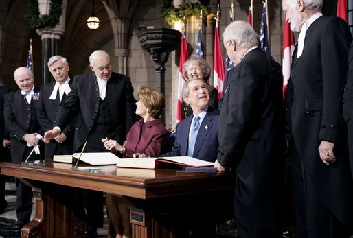 President George W. Bush and Laura Bush greet Parliament officials and sign guest books in the rotunda of Parliament Hill in Ottawa, Canada, Nov. 30, 2004.White House photo by Paul Morse