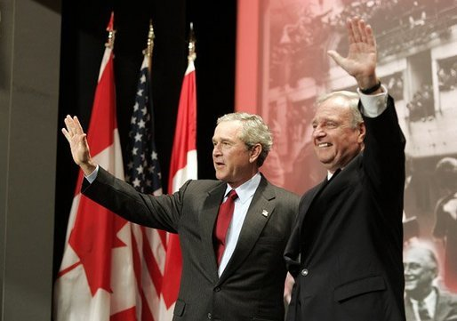 "President George W. Bush and Prime Minister Paul Martin wave after their remarks at Pier 21, Canada's historic point of immigration in Halifax, Canada, Dec. 1, 2004. During his remarks, President Bush thanked Canada for the hospitality to more than 33,000 passengers whose airplanes were diverted because of the 911 attacks. ""You opened your homes and your churches to strangers. You brought food, you set up clinics, you arranged for calls to their loved ones, and you asked for nothing in return,"" said the President.White House photo by Paul Morse"