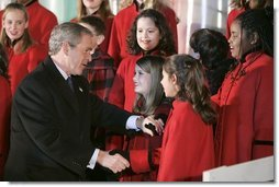 President George W. Bush greets members of the West Tennessee Youth Chorus during the National Christmas Tree lighting ceremony on the Ellipse in front of the White House Dec. 2, 2004.  White House photo by Paul Morse