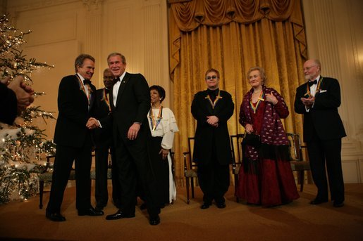 President George W. Bush greets Warren Beatty during a reception for the Kennedy Center Honors in the East Room of the White House, Sunday, Dec. 5, 2004. Also pictured, from left, are honorees Ossie Davis, Ruby Dee, Elton John, Joan Sutherland, and John Williams. White House photo by Eric Draper